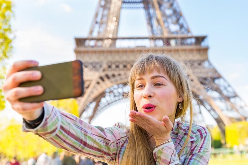 Tirando foto com o celular em frente à Torre Eiffel